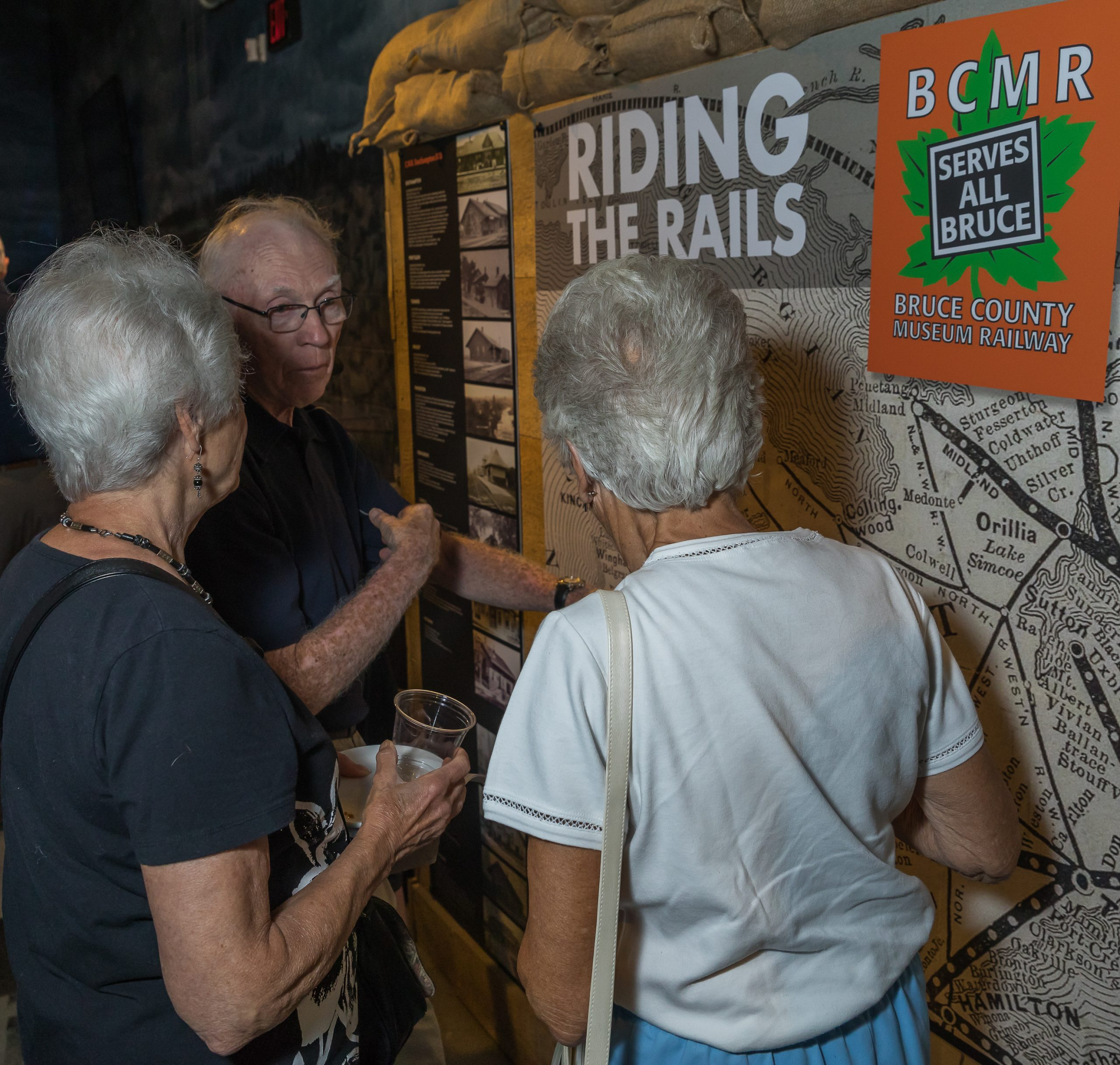photo of adults in front of the riding the rails map