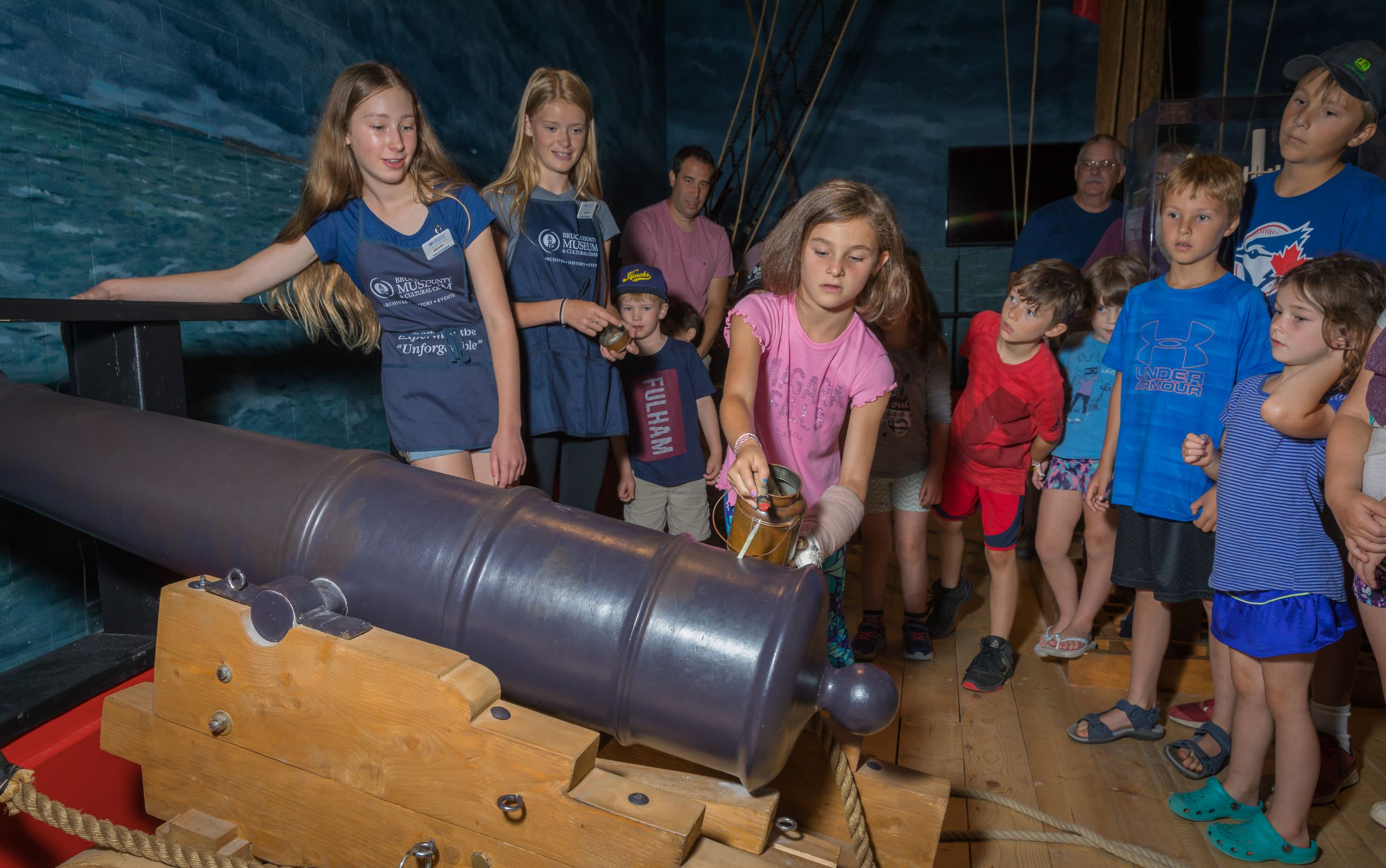 photo of group of kids preparing the light the cannon on HMS General Hunter replica boat