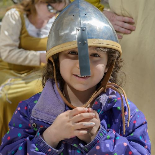 photo of child wearing medieval helmet