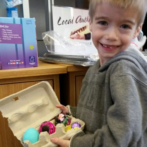 photo of boy showing his decorated easter eggs