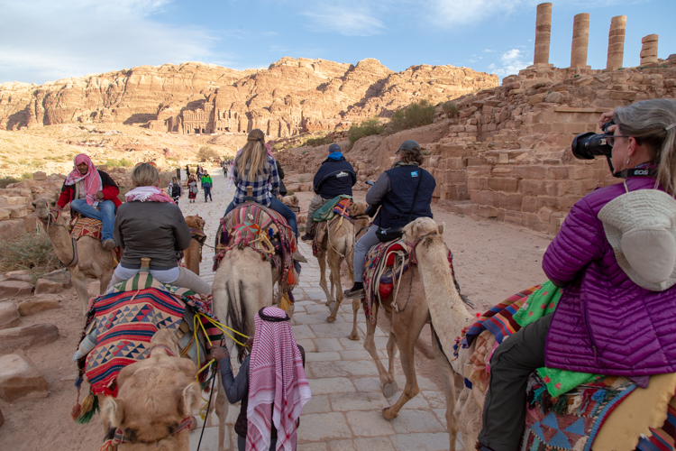 photo of people on camels in jordan