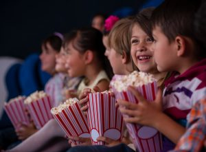 photo of kids eating popcorn at the movies