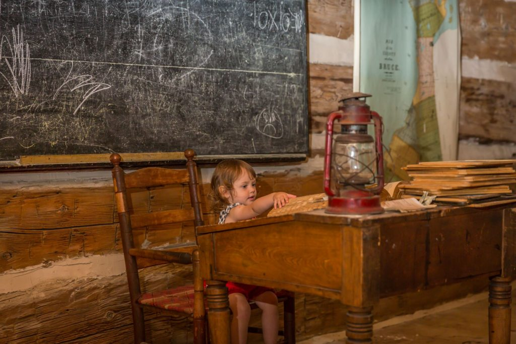 Photo of child at desk in school house