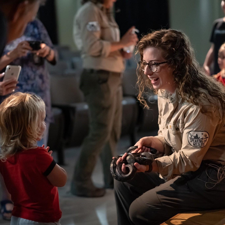 photo of speaking of wildlife presenter, snake and child