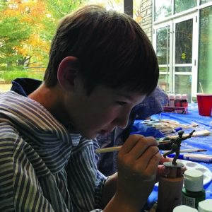 photo of boy painting small army figure