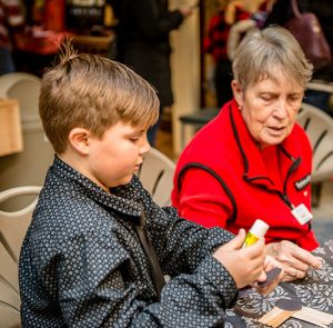 photo of a Lady helping a boy with a craft
