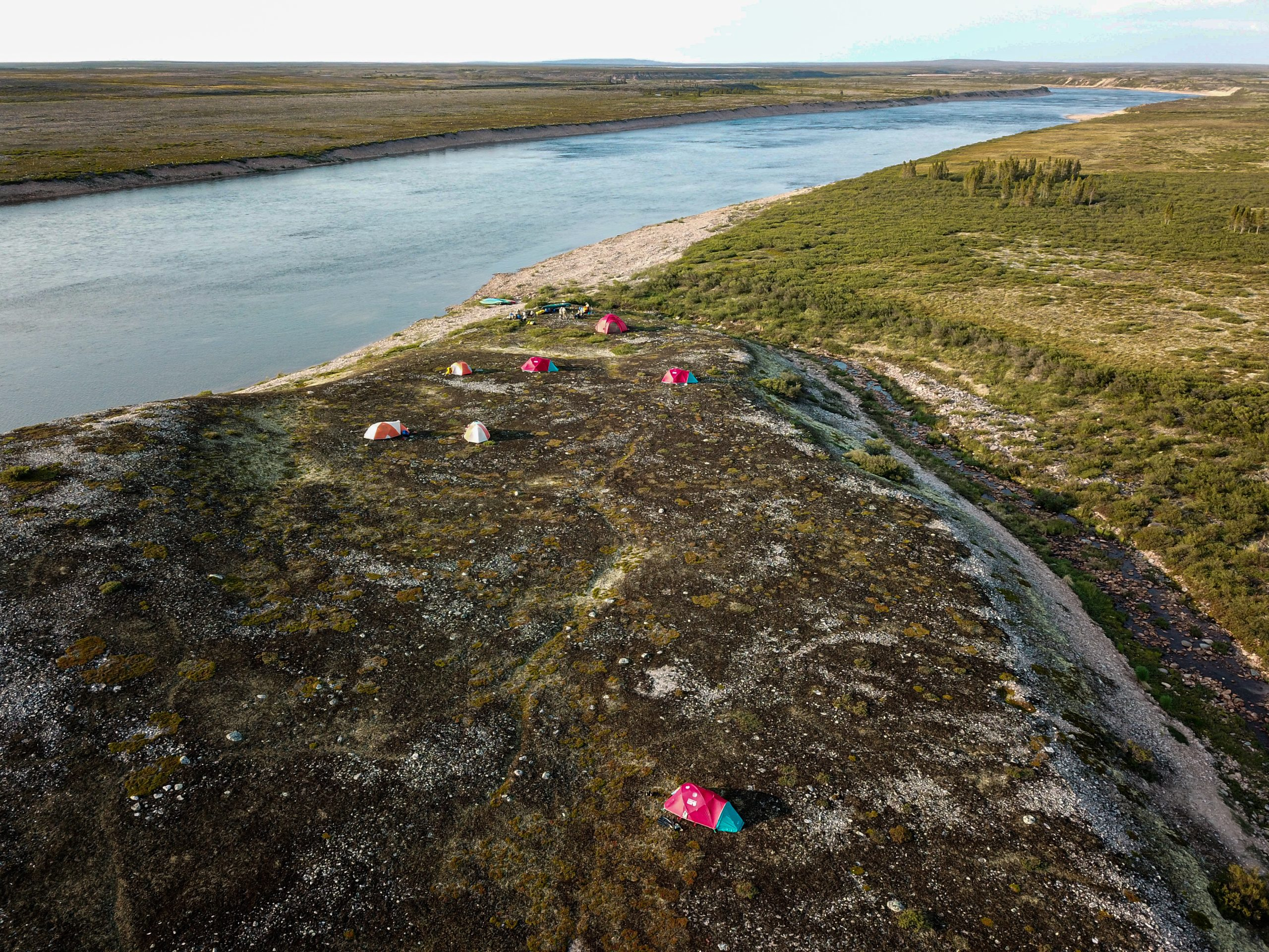 photo from above land with river and tents